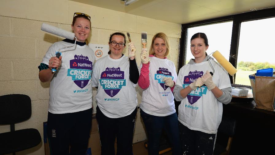 Brushes and rollers at the ready – England women's pace bowler Anya Shrubsole takes a break with volunteers at Denby