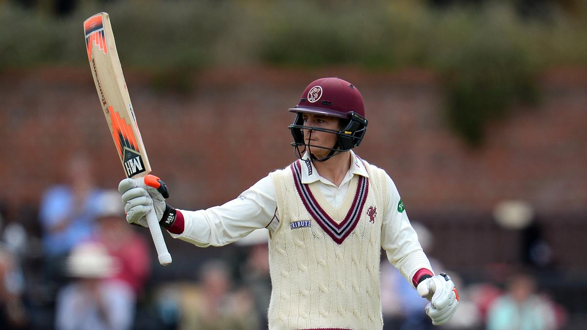 Somerset's young captain Tom Abell raises his bat after passing 50 against Surrey
