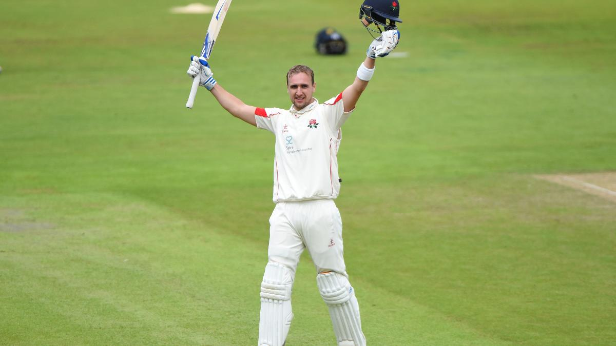 Liam Livingstone raises his bat after reaching his century for Lancashire