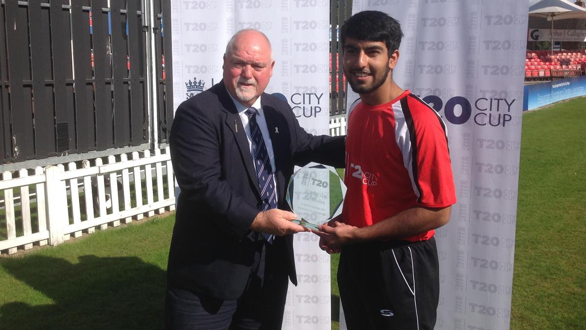 Adil Hussain receives the trophy from Mike Gatting