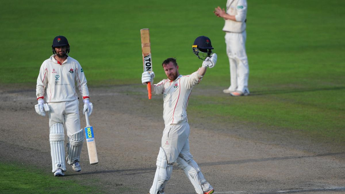 Lancashire's Steven Croft raises his bat after reaching his hundred