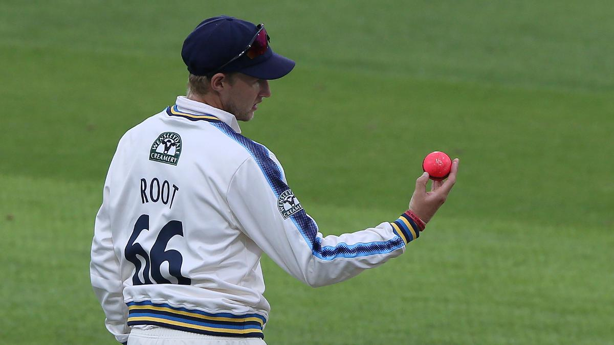 Joe Root examines a pink ball during Yorkshire's floodlit fixture with Surrey in 2017