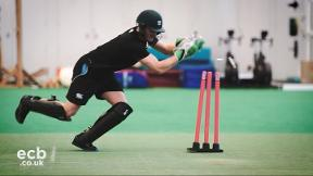 Should keepers stand in front or behind the stumps for run outs?