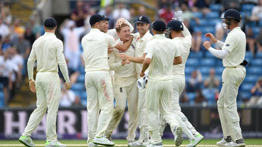 Dom Bess is mobbed by his England team-mates after picking up his first wicket in Test cricket