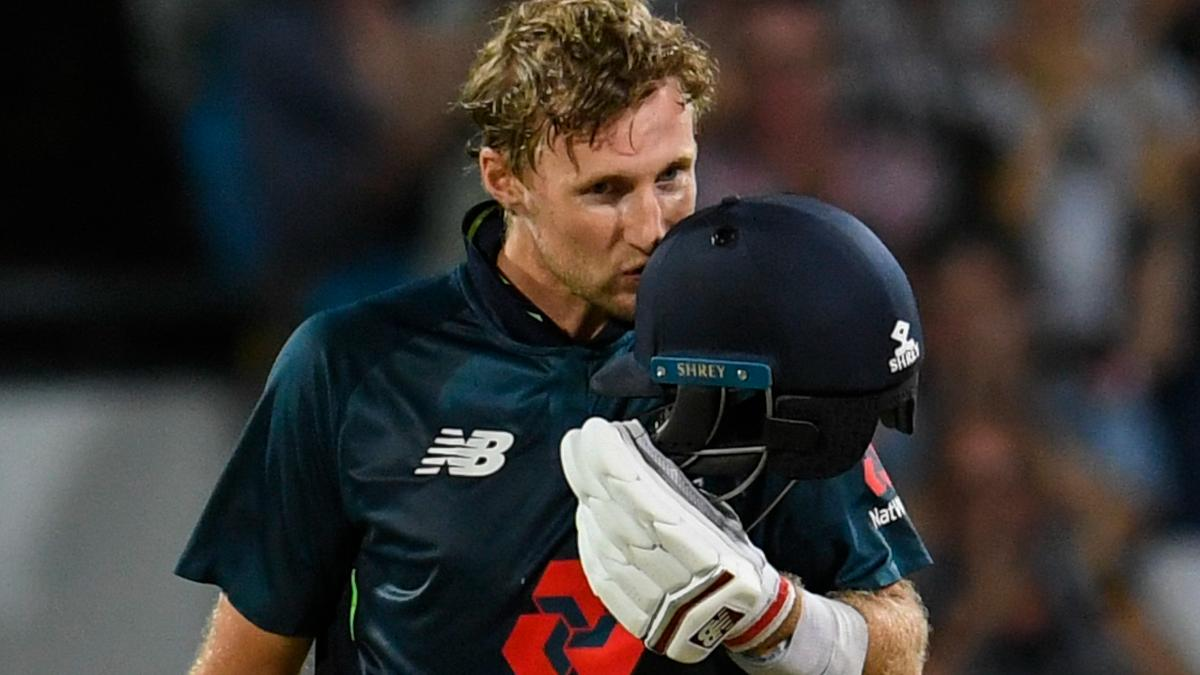Joe Root kisses the badge after reaching his century in Barbados